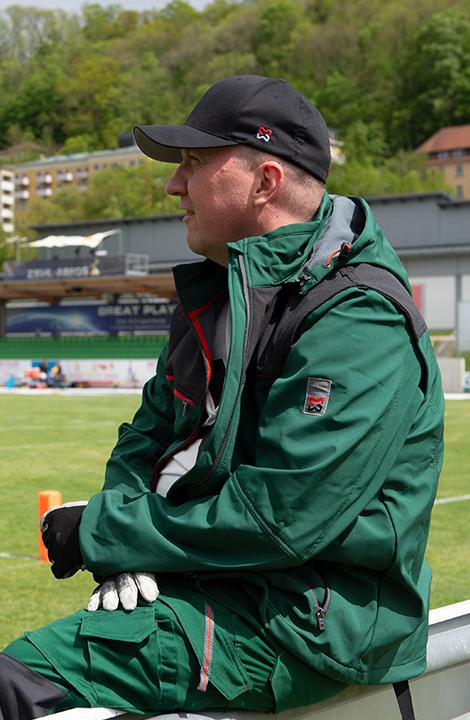 Master & Zeugwart Dennis trägt bei seiner Arbeit auf dem Football-Feld die flexible und wasserabweisende Stretch X Softshelljacke in grün.
