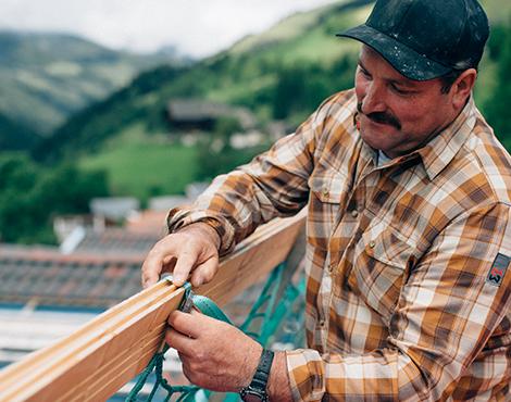 Der Dachdecker und Zimmerer ist mit dem braunen Nature Arbeitshemd und der schwarzen Cappy modern und zugleich schützend ausgstattet.