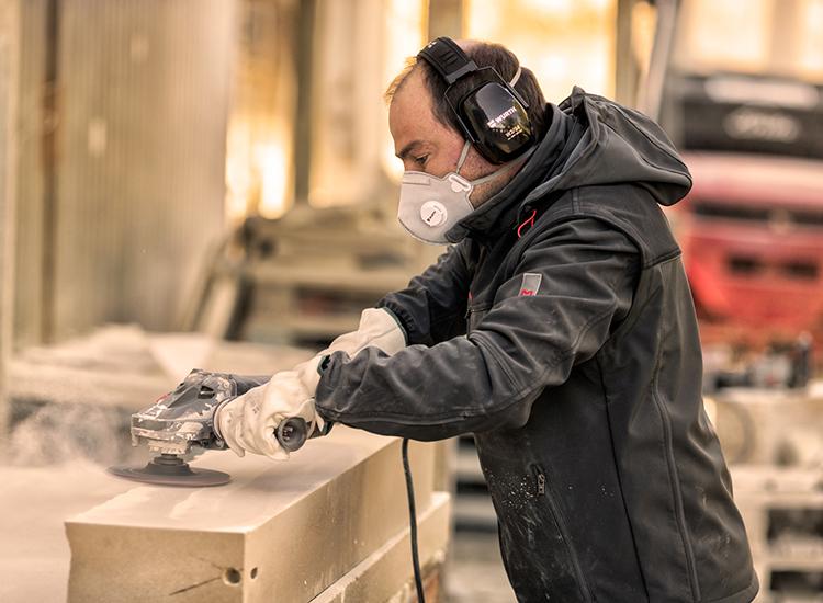 Der Kunsthandwerker & Maurer Ramón Solanes Fibla trägt die Arbeitsjacke der innovativen Stretch X Kollektion in Anthrazit