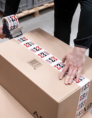 Lagermitarbeiter verpackt Workwear in Paket mit Logo-Paketband