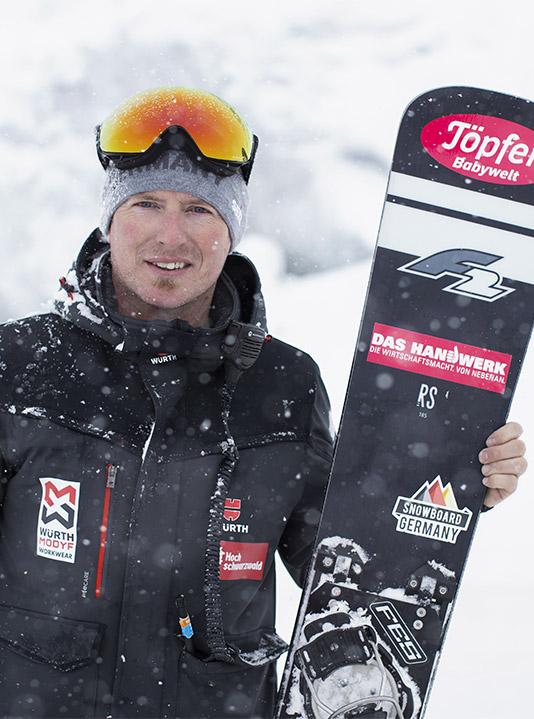 Master Martin Grüner trägt als Snowboard Techniker bei der Arbeit am liebsten die Stretch X Winter Softshelljace ode die Pilotenjacke Stretch X in Anthrazit.