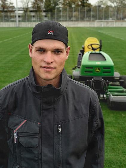 Master Pascal Lazarek trägt bei seiner Arbeit als Greenkeeper auf dem Fussballfeld die bequeme Stretch X Kollektion in Anthrazit.