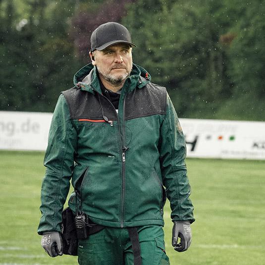 Master Thomas trägt bei seinen Vorbereitungen auf dem Footballfeld die grüne Stretch X Softshelljacke in Kombination mit der grünen Stretch X Bundhose.